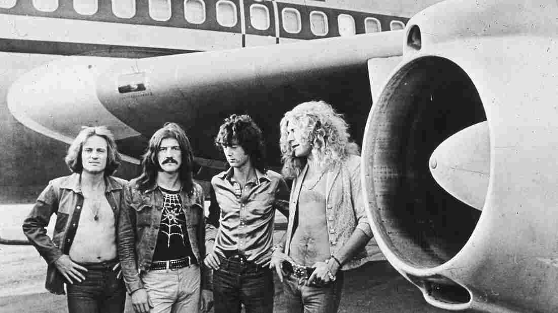 "British rockers Led Zeppelin pose in front of their private plane, dubbed ""The Starship,"" in 1973."