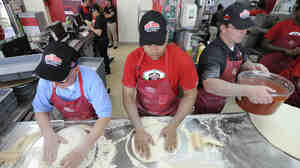 Employees at a Papa John's in New Hyde Park, N.Y., make pizzas in 2012. Restaurant employees have been a focus of debate on Obamacare coverage.
