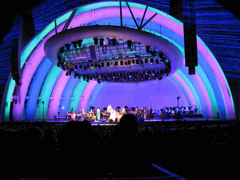 "Hollywood Bowl amphitheater, all lit up. On stage are members of the LA Philharmonic, Pink Martini - including BOTH of the band's lead singers, China Forbes (green dress) and Storm Large (white) - as well as the ""Japanese Barbra Streisand,"" Saori Yuki."