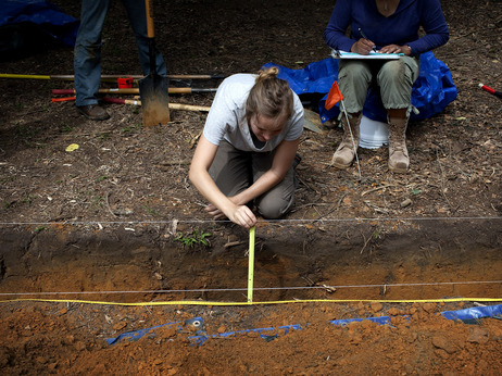 Meredith Tise, a graduate anthropology student at the University of South Florida, measures the depth of a trench dug at the site of the cemetery last May, as the university looks for signs of unmarked graves.