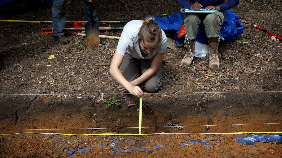 Meredith Tise, a graduate anthropology student at the University of South Florida, measures the depth of a trench dug at the site of the cemetery last May, as the university looks for signs of unmarked graves. (MCT/Landov)
