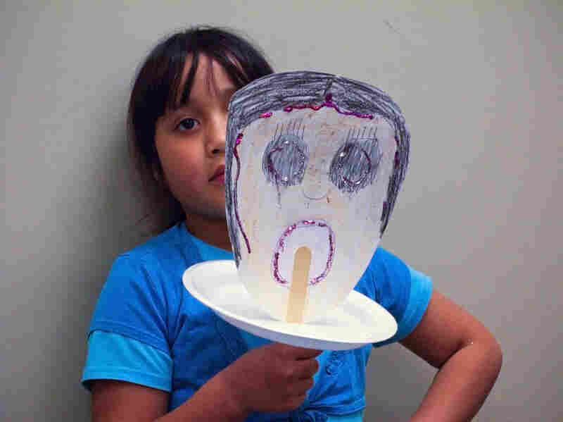 "Laura Molina, 9, shows the mask she created expressing the feeling of ""sadness."" Her mother is being treated for breast cancer at the Lyndon B. Johnson public hospital in Houston."