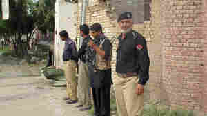 Pakistani policemen stand outside the central prison after an overnight attack in Dera Ismail Khan. Officials say Taliban insurgents freed hundreds of prisoners, including hard-line militants.