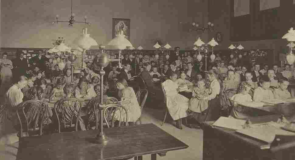 Patrons in the reading room of the Carnegie Library of Homestead in Munhall, Pa., circa 1900. The Carn