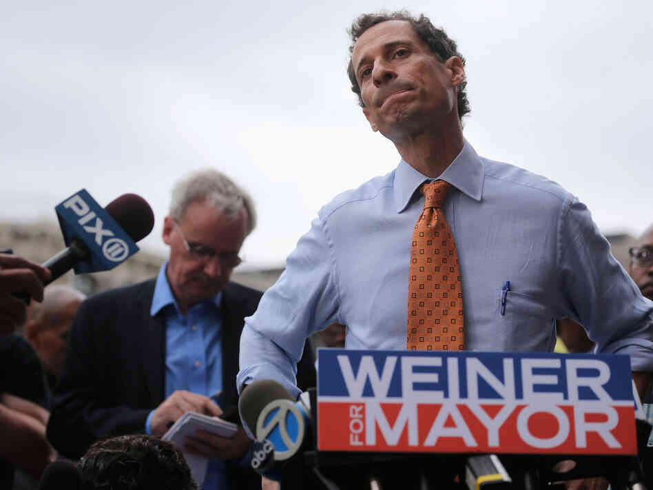 Anthony Weiner listens to a question from the media after courting voters outside a Harlem subway station in May.