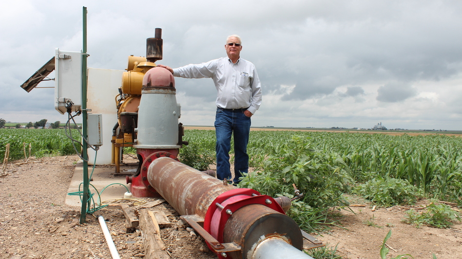 Jesse Garetson stands by one of his wells in Kansas. This one barely produces enough water to cool the engine, but many of Garetson's other wells pump more than 1,000 gallons of water per minute. (KCUR)