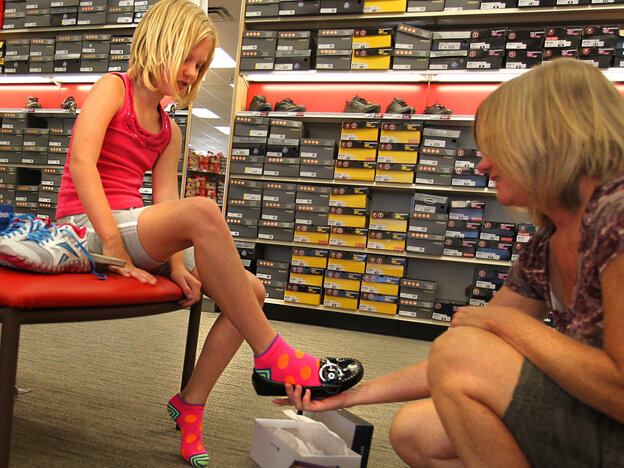 Chris Viehland helps her daughter Jenna try on shoes for the new school
