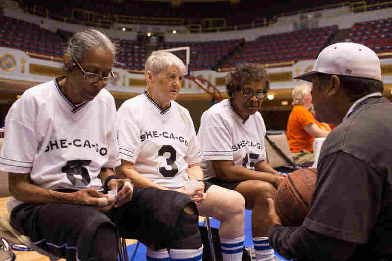 Coach Hugo Denado talks to his team, She-Ca-Go — Edwina Dennis (left), Roberta Leone and Cochran. The fourth and fifth players were unable to attend due to health problems, so the team played without any substitutes.