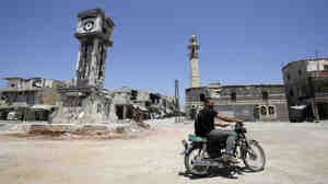 A Syrian man rides his motorbike past the Sunni Grand mosque on Thursday in the city of Qusayr, in Syria's central Homs province.