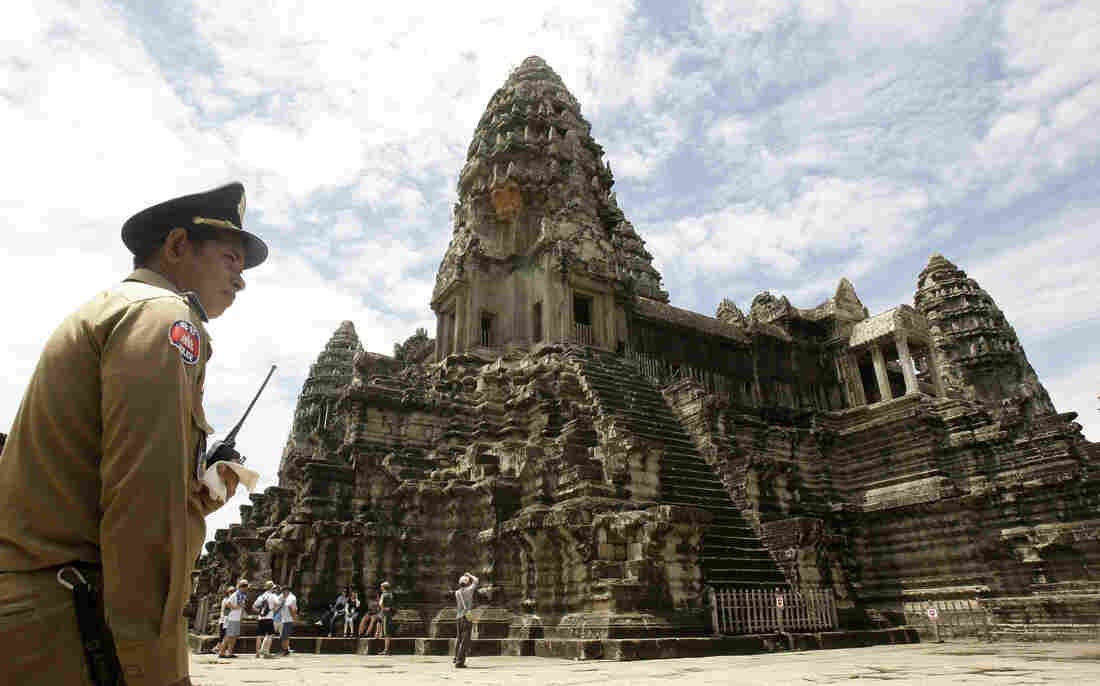 A police officer guards Cambodia's famed temple of Angkor Wat. The powerful city-state collapsed in 1431 after suffering through two decades of droughts.