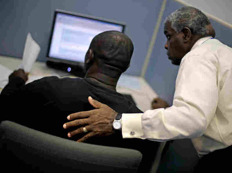 Employment Specialist Louis Holliday, right, helps an applicant file for unemployment at a Georgia Department of Labor career center last month in Atlanta. The jobless rate for African-Americans fell from 13.7 to 12.6 percent in July, but that's still twice the rate for whites.