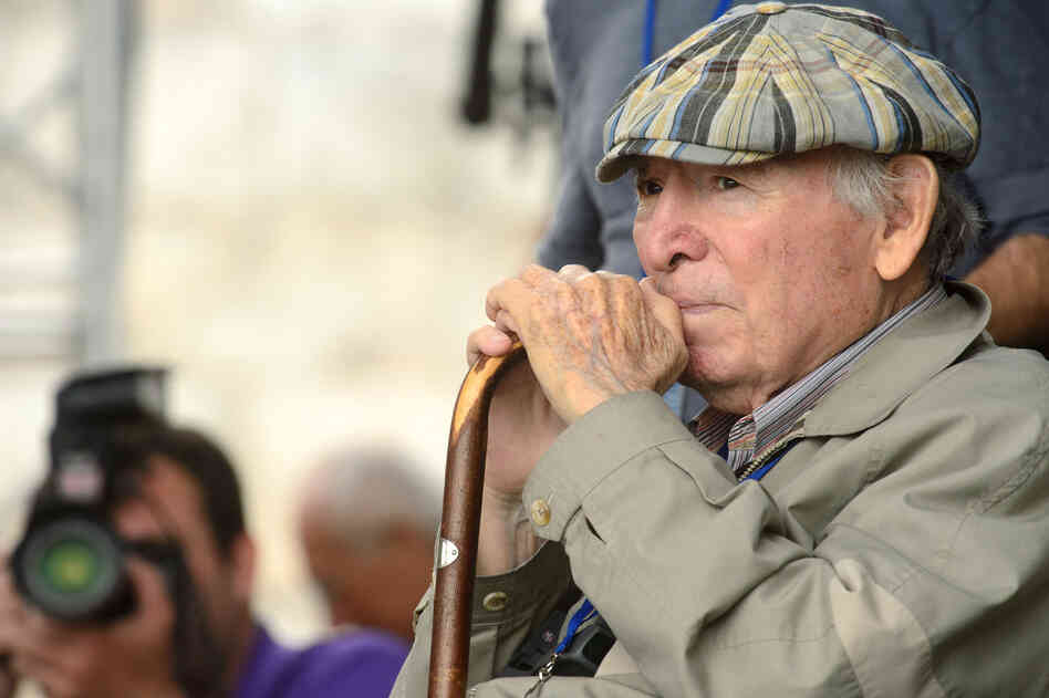 Newport Jazz Festival founder George Wein sits at the side of the stage as Wayne Shorter and Herbie Hancock play.