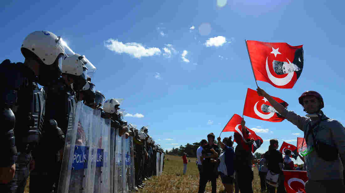 Protesters wave posters of Turkey's first president, Kemal Ataturk, before a police barricade outside the Silivri jail complex in Silivri, Turkey, on Monday. Scores of people were sentenced for their roles in what's being dubbed the Ergenekon plot.