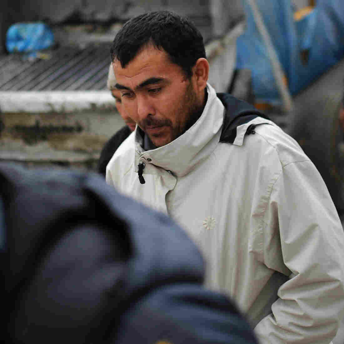 Migrant workers follow a police officer during a raid by Russian immigration authorities at a construction site in Moscow, in 2012.