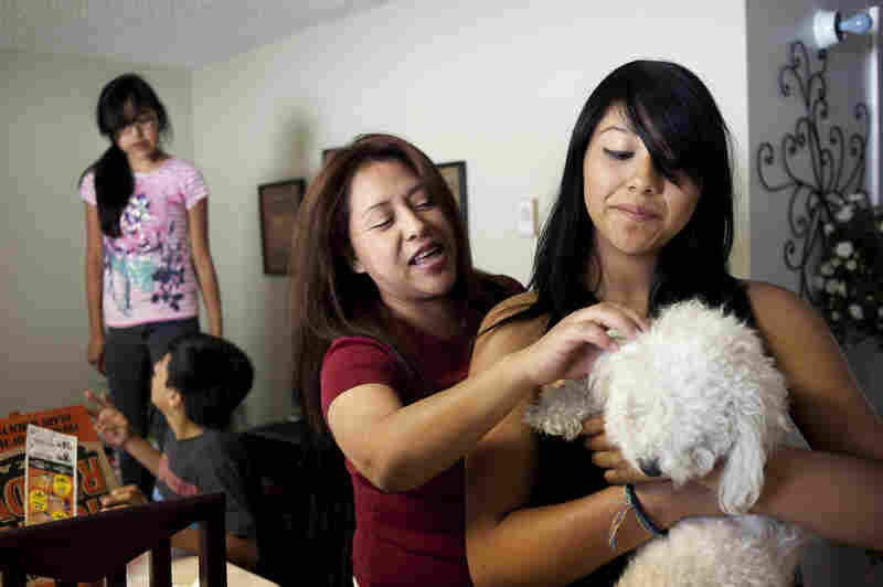 Liliana (Lily) Ramos reaches over her daughter toward her dog, Linda. Lily had heard pets help people deal with difficult situations, so she got the dog after she was ordered to be deported.