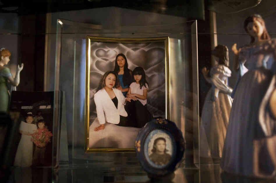 "A framed picture of Lily with her two girls at her home in Bend, Ore. Lily left the picture and her kids — Brian, Ashley and Karleen — with a relative when she was deported to Mexico. ""No quiero que sufren,"" she said. ""I don't want them to suffer."""