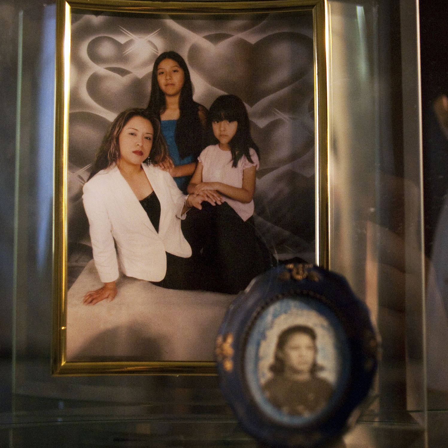 "A framed picture of Lily Ramos with her two girls at her home in Bend, Ore. She left the picture and her kids -- Brian, Ashley and Karleen -- with a relative when she was deported to Mexico. ""No quiero que sufren,"" she said. ""I don't want them to suffer."""
