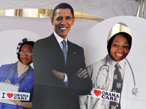 Two girls pose for a picture with a cardboard cut-out of President Obama in a tent defending