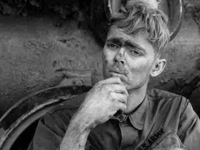 An American soldier reads a letter from home, while taking a break from repairing a tank tread in Lang Vei, Vietnam, in March 1971.
