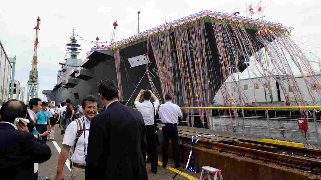 Japan's new warship, the Izumo, draws a crowd for its launch ceremony at the port in Yokohama Tuesday. At 248 meters (814 feet) in length, the flat-topped ship has been called a destroyer, or a helicopter carrier.