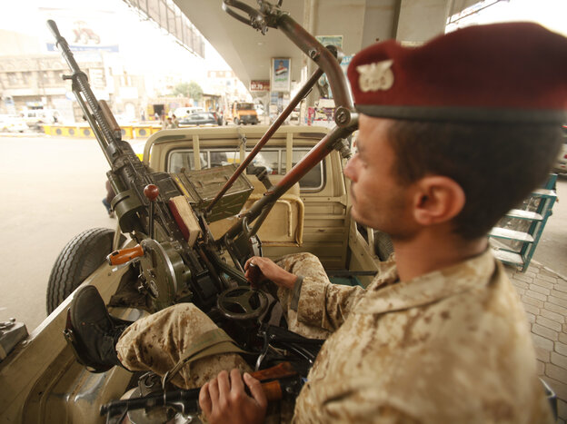 An army trooper sits beside a machine gun that is mounted on a patrol vehicle at a checkpoint in Sanaa, Yemen. Security is tight in the capital amid warnings about possible terrorist attacks.