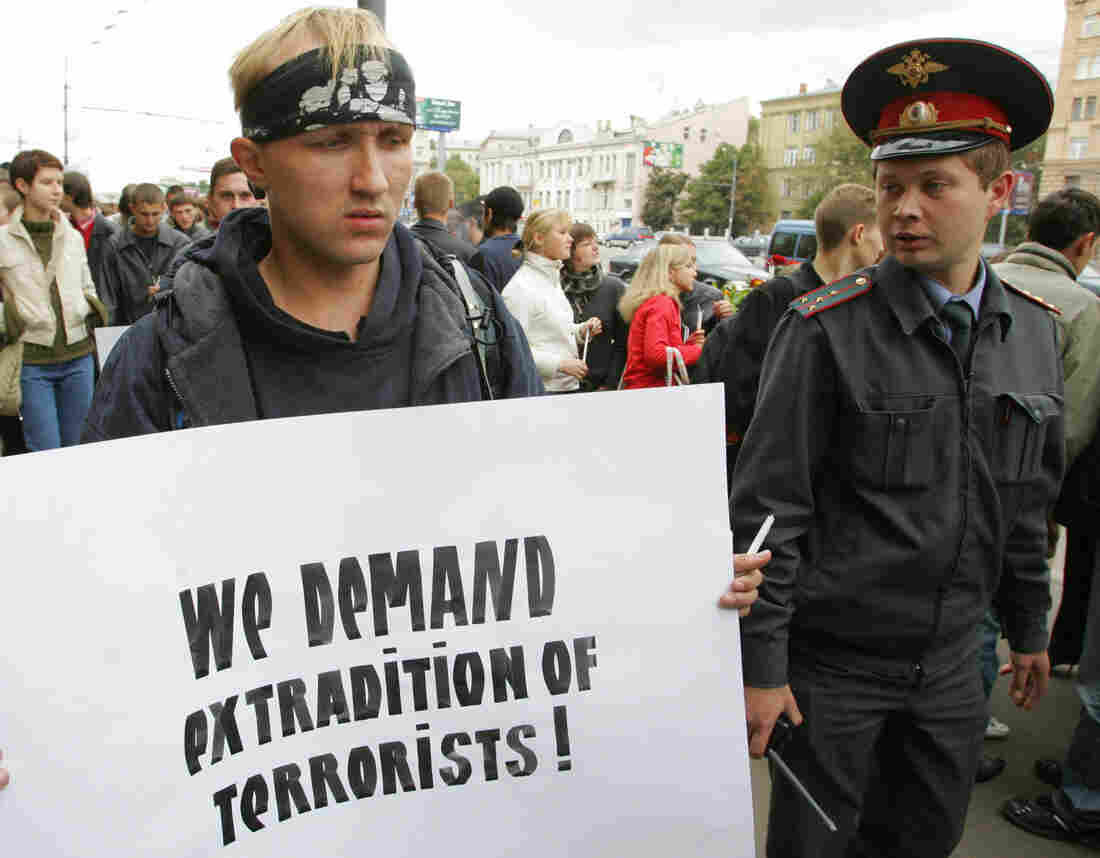 A Russian police officer watches a protester during a rally in front of the U.S. Embassy in Moscow in September 2004. Some 500 protesters demanded the extradition of Ilyas Akhmadov from the United States.