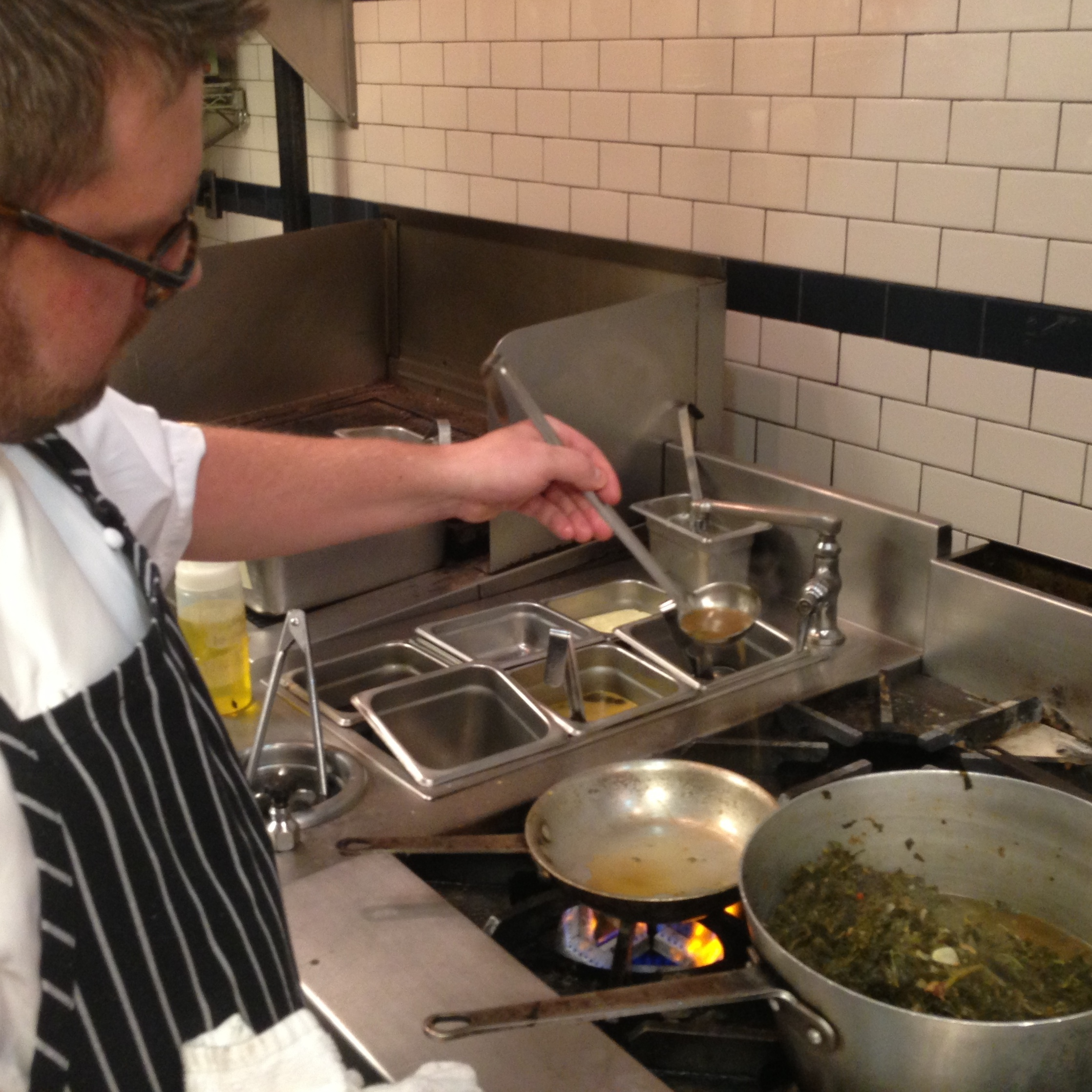 Chef James Huff of Pearl Dive restaurant ladles up some pot liquor fresh from a steaming pot of sauteed collard greens and kale.