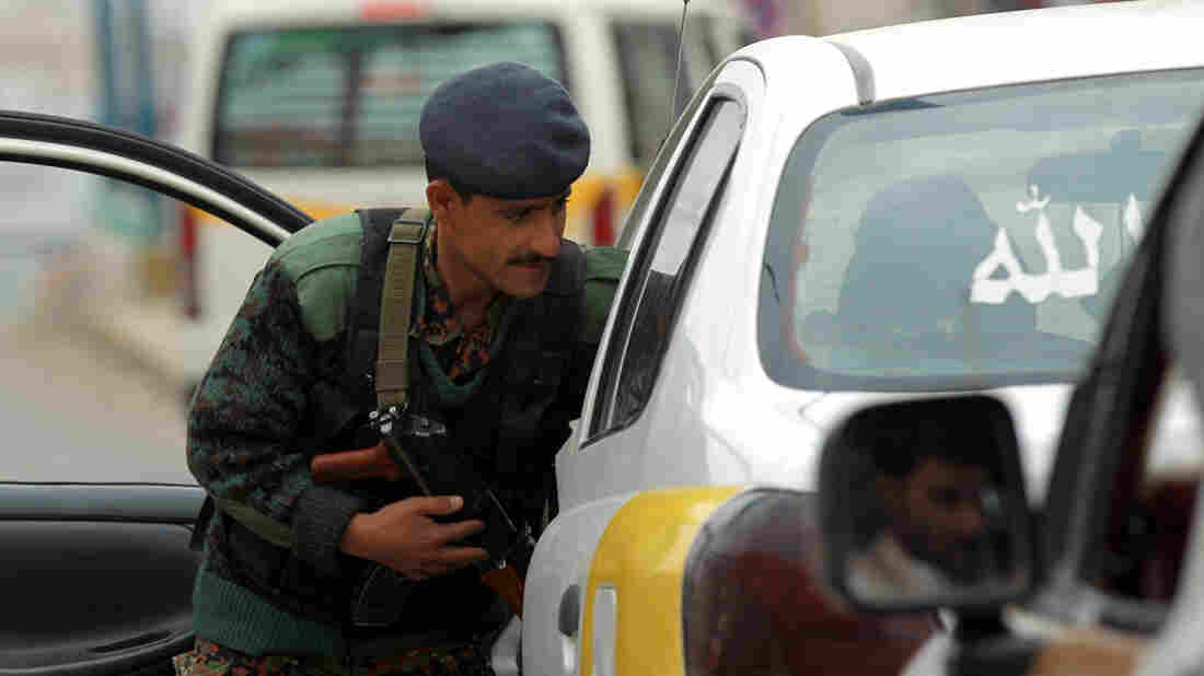 A Yemeni soldier searches a car near the airport in the capital, Sanaa. The United States has ordered Americans to leave Yemen immediately amid a warning of a possible attack.
