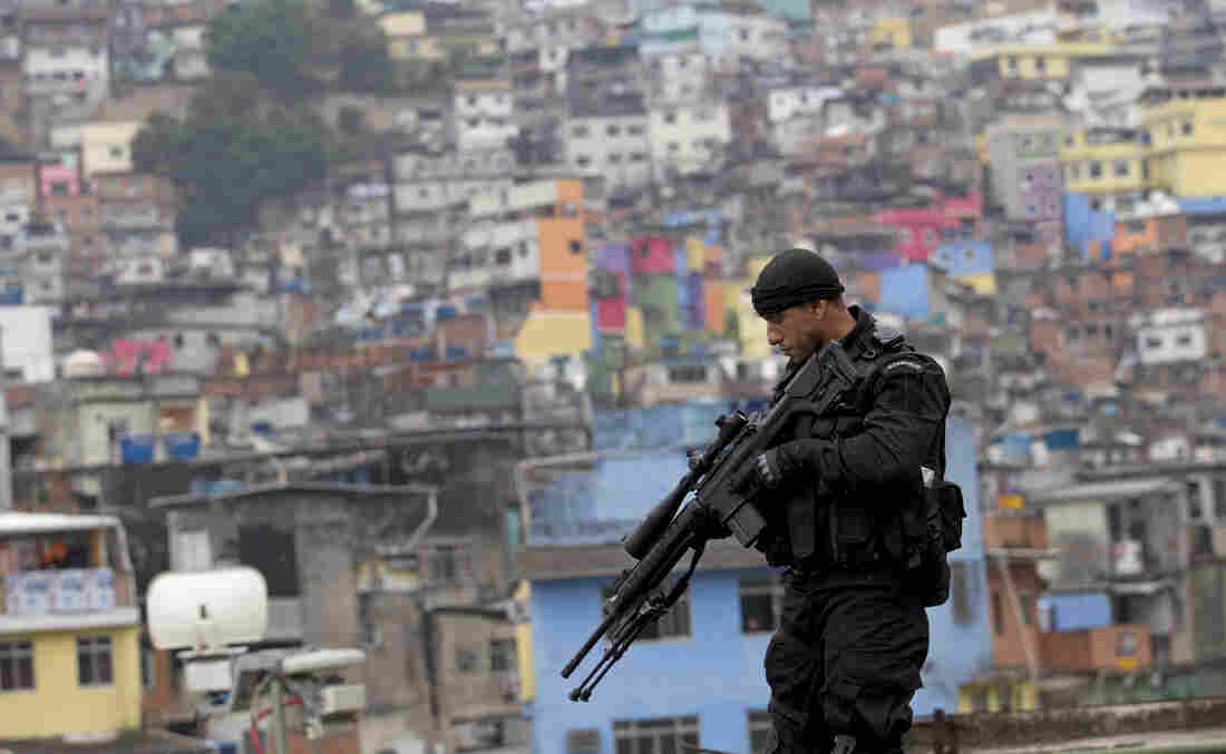 """A police officer patrols the rooftop of a school at the Rocinha slum in Rio de Janeiro, Brazil, on Sept. 20, 2012, where a """"pacification"""" anti-crime effort was underway. Rio police are now going to attempt a similar pacification in another huge slum, Mare."""