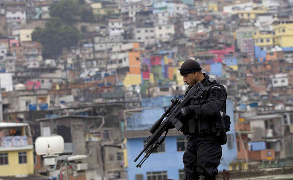 "A police officer patrols the rooftop of a school at the Rocinha slum in Rio de Janeiro, Brazil, on Sept. 20, 2012, where a ""pacification"" anti-crime effort was underway. Rio police are now going to attempt a similar pacification in another huge slum, Mare."
