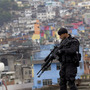 "A police officer patrols the rooftop of a school at the Rocinha slum in Rio de Janeiro, Brazil, on Sept. 20, 2012, where a ""pacification"" anti-crime effort was underway. Rio p"