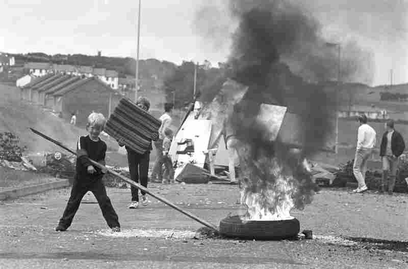 Children burn tires and block Flying Horse Road, in Downpatrick, Co. Down, 1980s.