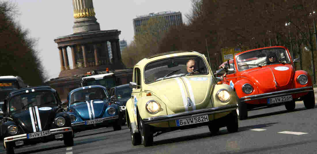 Beetle cars of German car maker Volkswagen (VW) drive past Berlin's landmark the Victory Column on April 23, 2013, in Berlin to promote a new tourist attraction.