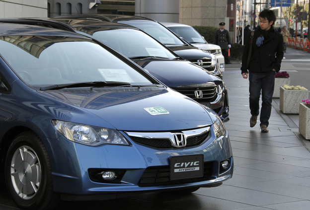 Sayonara, Civic: A man looks at Honda Civic hybrid cars in front of the Japanese automaker's headquarters in Tokyo, Japan, on Jan. 30, 2010.