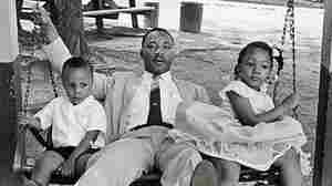 Martin Luther King Jr sits on a swing with his eldest daughter, Yolanda, and eldest son, Martin, at an amusement park he helped desegregate.