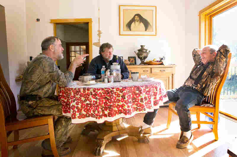 Michael Lewis (from left), Roy Savage and Thomas Ball enjoy coffee and conversation after coming in from hunting. Lewis and Ball do not see the natural gas drilling that takes place on Savage's land as a threat to the sport they love.