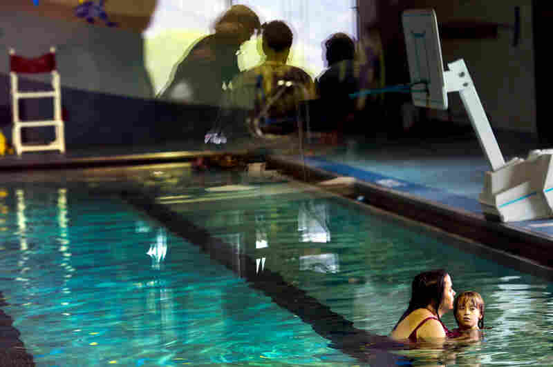 Michelle swims with her daughter Regan at the Battlement Mesa Community Center as concerned citizens discuss natural gas drilling in the area during the Western Colorado Congress annual meeting. The community center was fully paid for by the oil and gas company Exxon. Garfield County has been one of the largest producers of natural gas in Colorado.