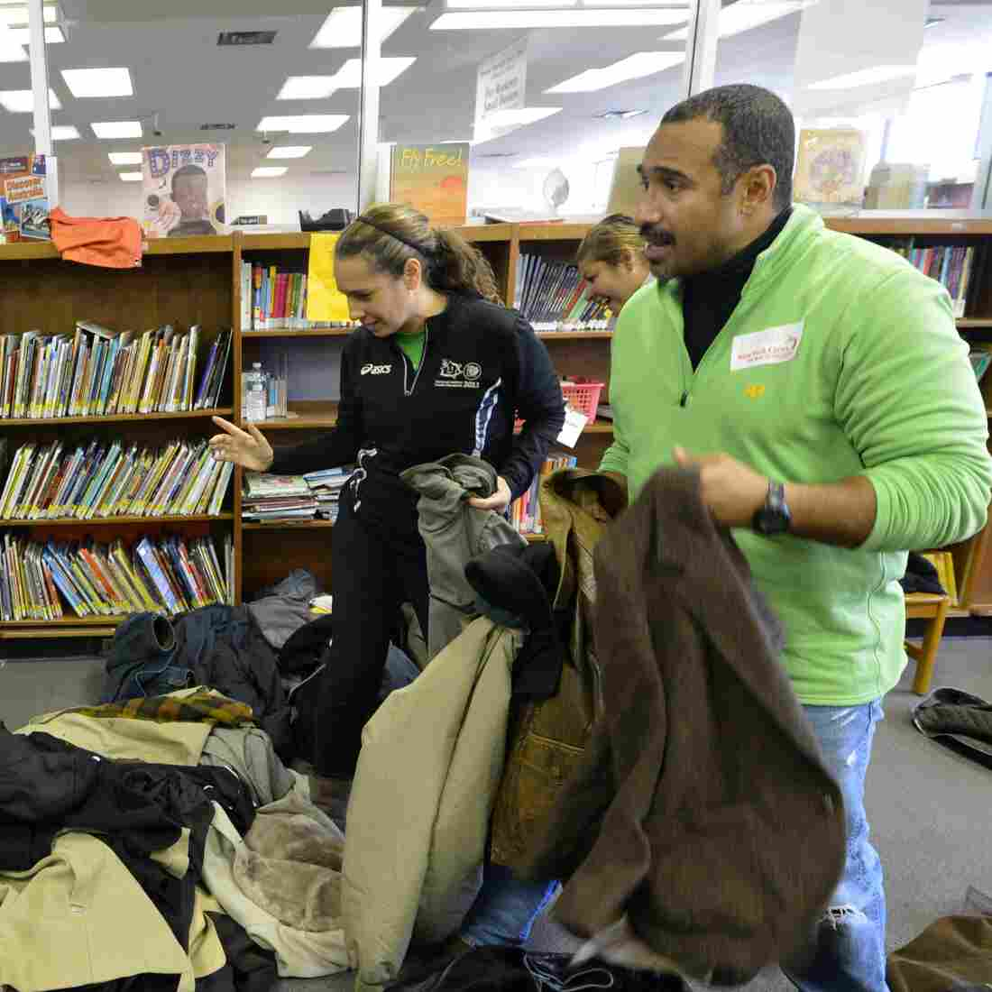 Volunteers at the Queens Library in the Far Rockaway section of Queens hand out coats to people affected by Hurricane Sandy.