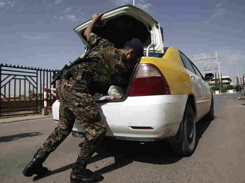 A police officer checks a car Wednesday at the entrance of Yemen's Sanaa International Airport. Security forces in the Middle East and Africa have been on heightened alert because of concerns about potential terrorist attacks.