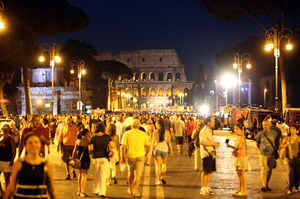 People walk along Rome's Via dei Fori Imperiali during
