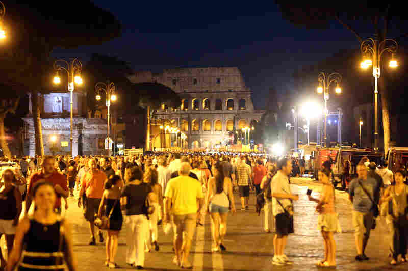 "People walk along Rome's Via dei Fori Imperiali during ""La Notte dei Fori"" on Saturday. The event opened a plan to ban private traffic from the stretch of roadway near the Colosseum."