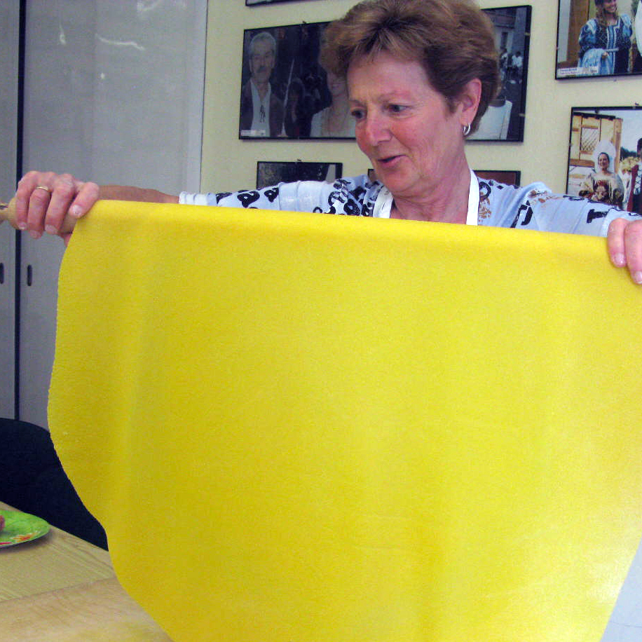 Grazia Battistini presents the sheet of fresh egg pasta, known as sfoglia, that she rolled out by hand to make belly-button shaped tortellini.