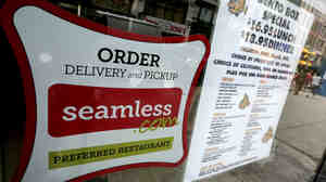 A Seamless sticker is displayed next to the menu in the window of a restaurant in New York's Times Square on Saturday. Rivals Seamless and GrubHub said Friday that they have completed their combination, creating an online takeout company covering about 25,000 restaurants in 500 cities.