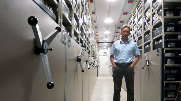 Dave Dierig, research leader at the National Center for Genetic Resources Preservation, stands among the ceiling-high shelves that hold the 600,000 seed packets in this cold storage vault. (KUNC)