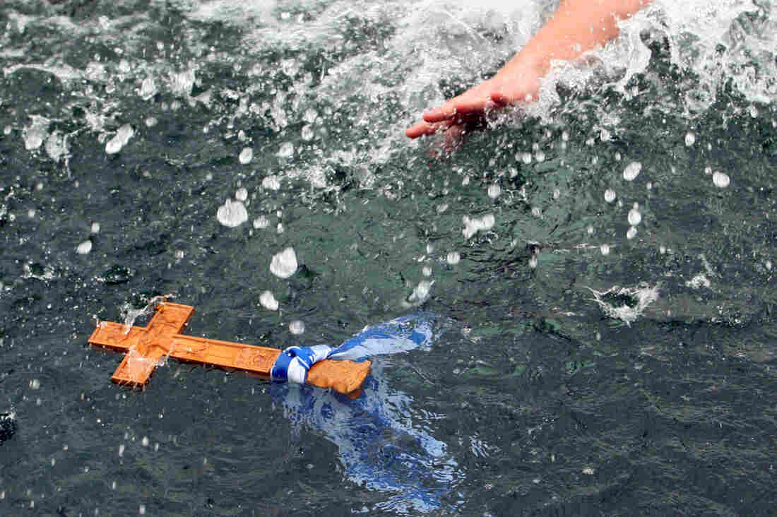 A man reaches for a wooden cross in the sea during an Epiphany ceremony in the Greek port of Thessaloniki on January 6, 2011.