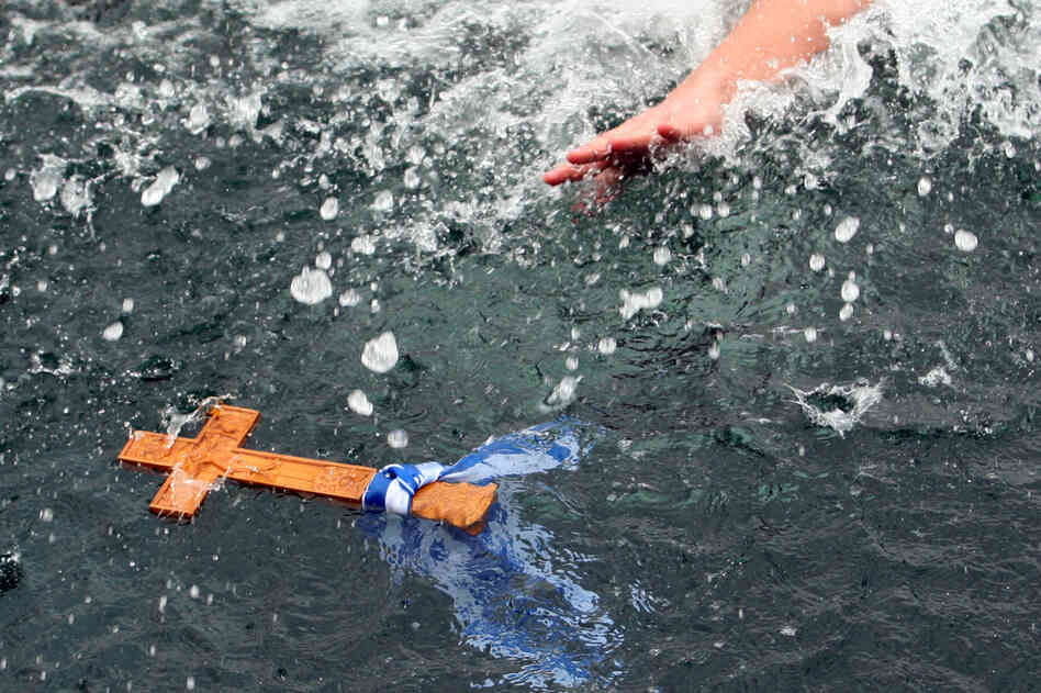 A man reaches for a wooden cross in the sea duri