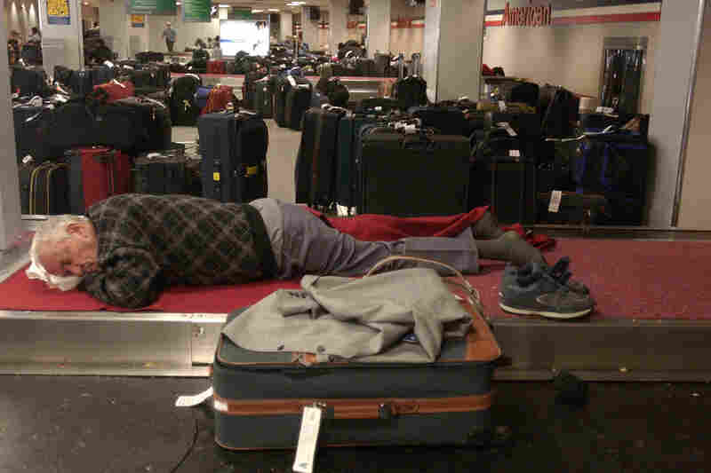 A stranded traveler sleeps in the baggage claim area at John F. Kennedy International Airport. The power outage caused flight delays at airports in New York City, stranding travelers for up to 48 hours.