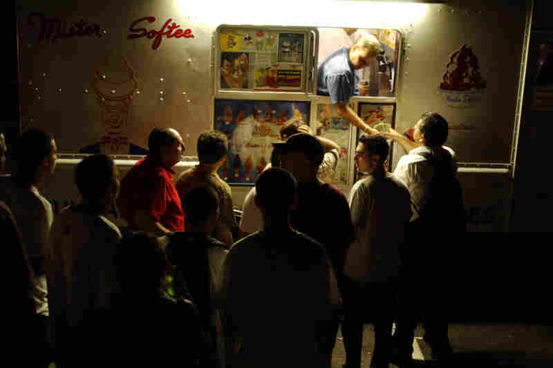 Patrons crowd a Mister Softee ice cream truck to buy ice cream as darkness envelops Weehawken, N.J.
