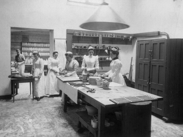 Maids at work in a large kitchen, circa 1890.