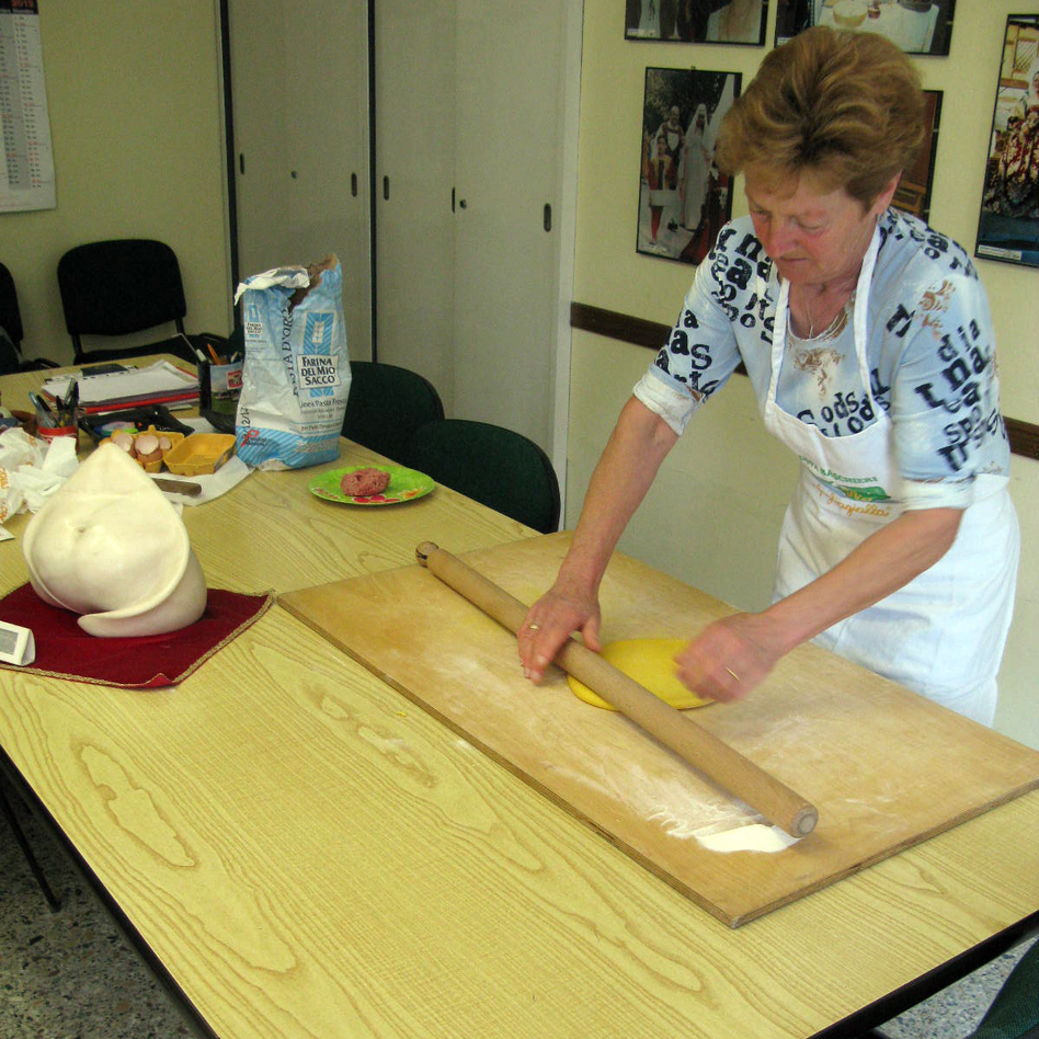 Grazia Battistini, 63, has been been making tortellini as a sfoglina for about 50 years. A statue of the ideal tortellino shape sits in the foreground. (NPR)